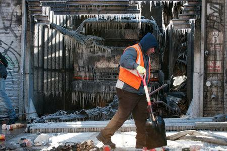 FILE PHOTO: A worker cleans up after a large fire extinguished by the New York Fire Department (NYFD) as they worked in frigid conditions in the Brooklyn Borough of New York, U.S., January 31, 2019. REUTERS/Lloyd Mitchell/File Photo
