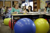 Students in Robbi Giuliano's fifth grade class sit on yoga balls as they complete their assignments at Westtown-Thornbury Elementary School Monday, Feb. 4, 2013, in West Chester, Pa. The exercise gear is part a larger effort to modernize schools based on research linking physical activity with better learning, said John Kilbourne, a professor of movement science at Grand View State University in Allendale, Mich. (AP Photo/Matt Rourke)