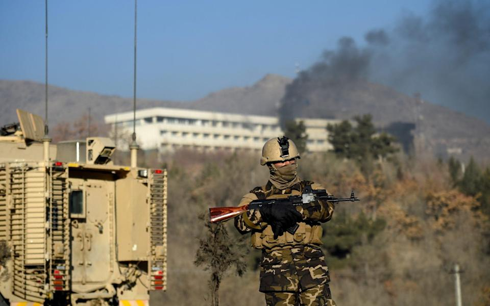 An Afghan security personnel stands guard as smoke billows from the Intercontinental Hotel during a fight between gunmen and Afghan security forces in Kabul on January 21, 2018 - WAKIL KOHSAR/AFP