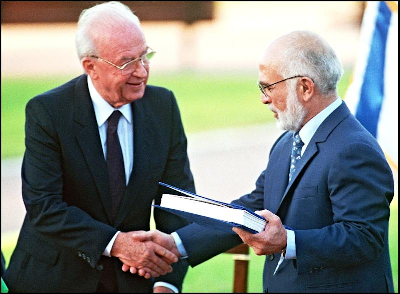 Jordan's King Hussein (R) and Israeli Premier Yitzhak Rabin (L) shake hands after they exchanged the documents of their countries' 1994 peace treaty on the shore of the Sea of Galilee (AFP Photo/SVEN NACKSTRAND)