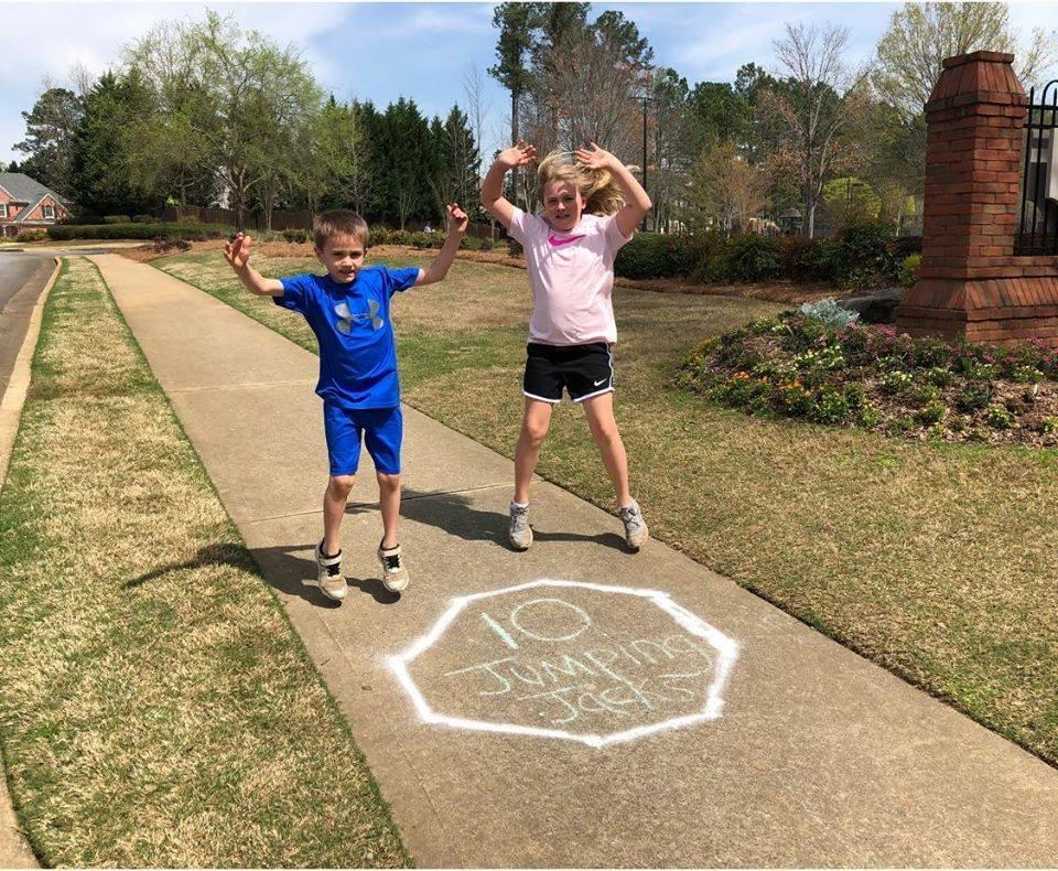Mackenzie and Maddox Germany do jumping jacks in a makeshift circuit loop created by a physical therapist in the neighborhood. (Photo: Teri Germany)
