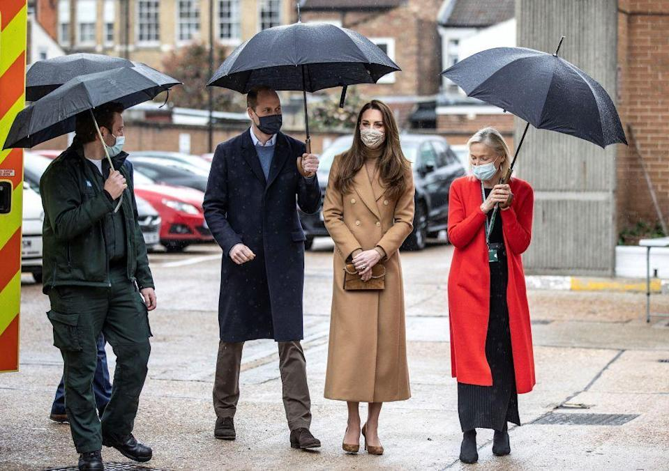 """<p>The Duchess of Cambridge opted for a monochromatic look for <a href=""""https://www.townandcountrymag.com/society/tradition/a35874683/kate-middleton-camel-coat-newham-ambulance-station-photos/"""" rel=""""nofollow noopener"""" target=""""_blank"""" data-ylk=""""slk:a visit with first responders"""" class=""""link rapid-noclick-resp"""">a visit with first responders</a> at an ambulance station in London. She paired her camel ensemble with a floral face mask and suede camel heels to match her clutch.</p>"""