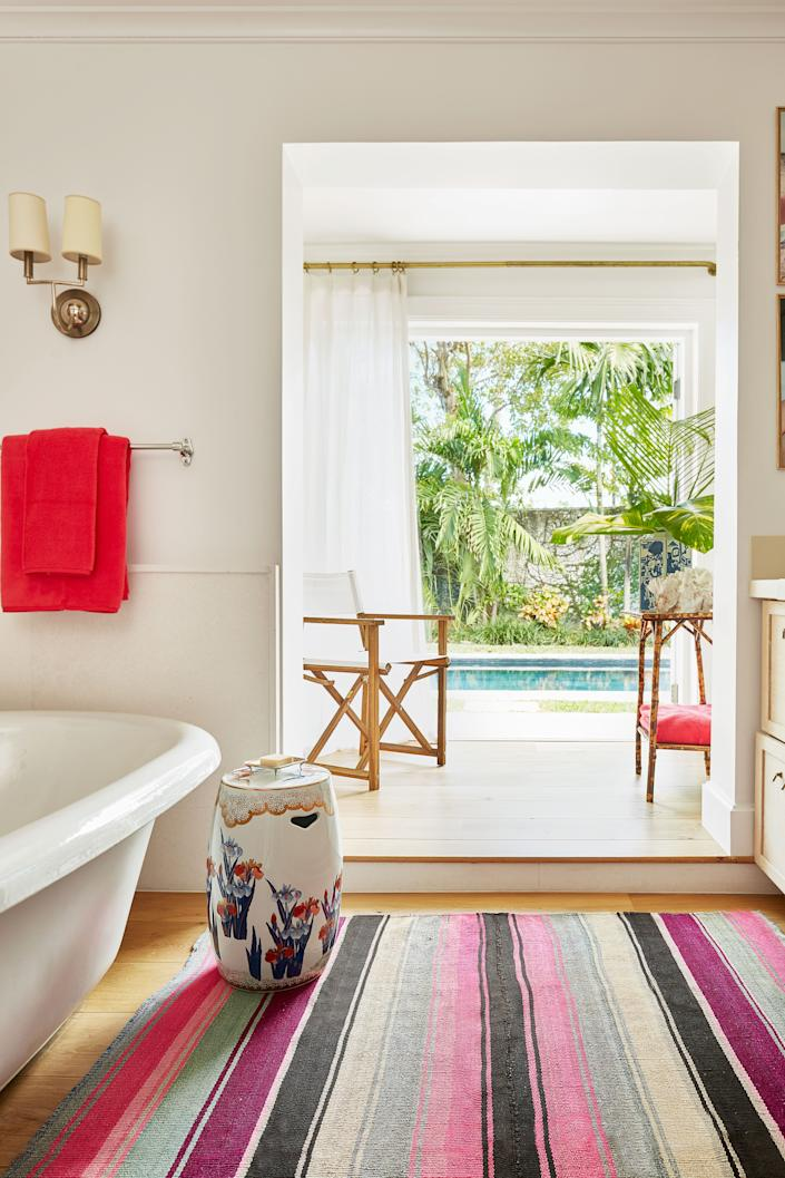 "<div class=""caption""> The master bath offers a view of the pool. Vintage side table and rug; <a href=""https://www.matouk.com/"" rel=""nofollow noopener"" target=""_blank"" data-ylk=""slk:Matouk"" class=""link rapid-noclick-resp"">Matouk</a> towels. </div>"