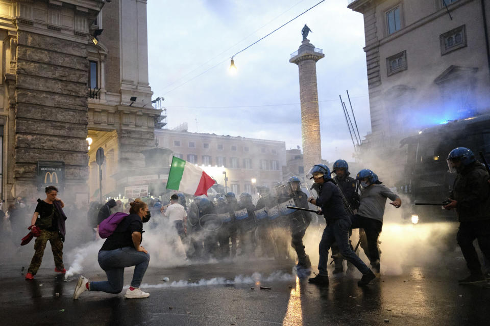 Demonstrators and police clash during a protest, in Rome, Saturday, Oct. 9, 2021. Thousands of demonstrators protested Saturday in Rome against the COVID-19 health pass that Italian workers, both the public and private sectors, must display to access their workplaces from Oct. 15 under a government decree. (Mauro Scrobogna/LaPresse via AP)