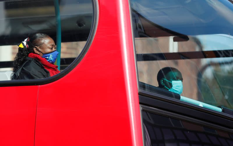 A woman wearing a face mask travels on a bus in London