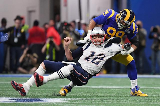<p>Tom Brady #12 of the New England Patriots is sacked by Aaron Donald #99 of the Los Angeles Rams in the first quarter during Super Bowl LIII at Mercedes-Benz Stadium on February 3, 2019 in Atlanta, Georgia. (Photo by Harry How/Getty Images) </p>