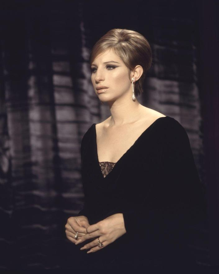 """<p>Barbra Streisand's sleek bouffant and black gown make her diamond teardrop earrings the star of the show in this chilling performance of """"My Man"""" in <em>Funny Girl</em>. </p>"""