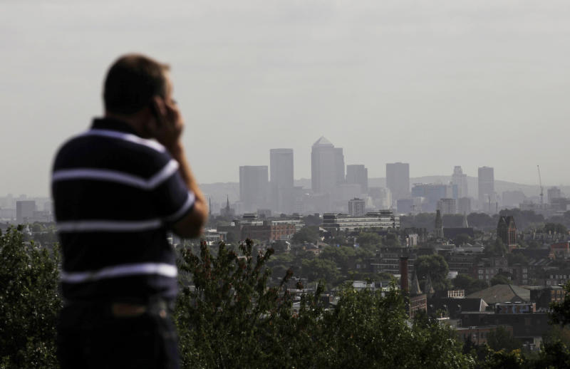 FILE In this Friday, Sept. 23, 2011 file photo a man talks on a mobile phone as the hi-rise buildings of the banks based in the Canary Wharf business district are seen in the distance from Parliament Hill on Hampstead Heath in London. British officials have given their word: 'We won't read your emails.' But experts say that its proposed new surveillance program, unveiled last week as part of the government's annual legislative program, will gather so much data that spooks won't have to read your messages to guess what you're up to. (AP Photo/Matt Dunham)