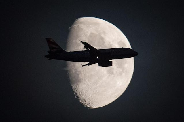 <p>A passenger aircraft flies in front of the moon over central London. (PA Images) </p>