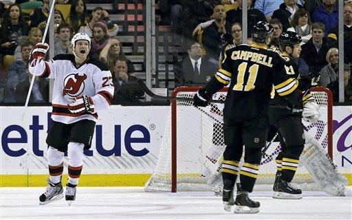New Jersey Devils center David Clarkson, raises his stick after his goal as Boston Bruins center Gregory Campbell (11) skates past during the second period of an NHL hockey game in Boston, Tuesday, Jan. 29, 2013. (AP Photo/Charles Krupa)