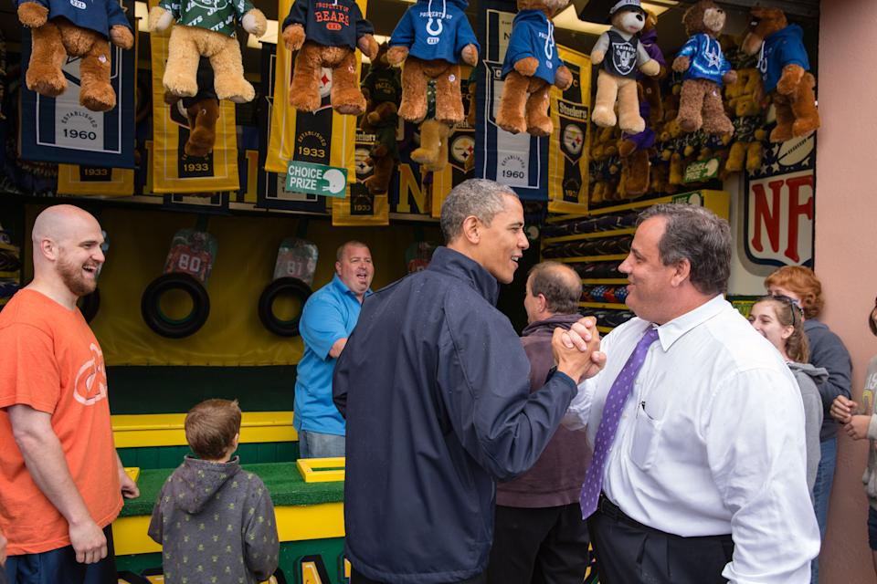 "WASHINGTON, DC - MAY 28: In this handout provided by the White House, U.S. President Barack Obama (C) congratulates New Jersey Governor Chris Christie (R) while playing the ""TouchDown Fever"" arcade game along the Point Pleasant boardwalk May 28, 2013 in Point Pleasant Beach, New Jersey. Seven months after Superstorm Sandy devastated the region, President Obama declared that the Jersey Shore is back in an appearance with the governor. (Photo by Pete Souza/White House via Getty Images)"