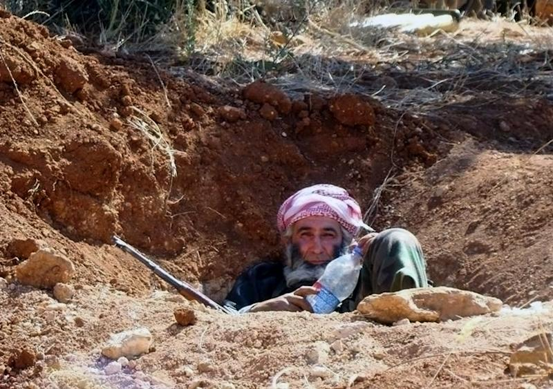 "This citizen journalism image provided by Edlib News Network, ENN, which has been authenticated based on its contents and other AP reporting, shows an elderly Syrian rebel sit in a trench, in Idlib province, northern Syria, Wednesday, June 12, 2013. Syrian rebels have attacked a village in the country's east, killing dozens of Shiites, mostly pro-government fighters, activists said Wednesday. A Syrian government official denounced the attack, saying it was a ""massacre"" of civilians. (AP Photo/Edlib News Network ENN)"