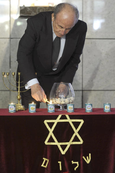 Aleksandar Sumkovski, an 88-year old Macedonian Jew, lights candles in memory of victims of the Holocaust, in the Holocaust Memorial center of the Jews of Macedonia in the country's capital Skopje, on Thursday, April 19, 2012. Sumkovski's mother was among the 7,144 Macedonian Jews who were killed in the Nazi extermination camp of Treblinka. (AP Photo/Boris Grdanoski)