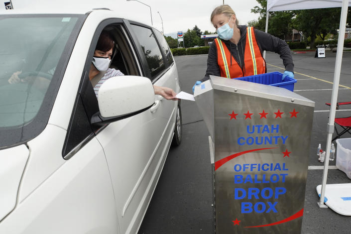 A women is helped by an election worker to put her ballot in a box