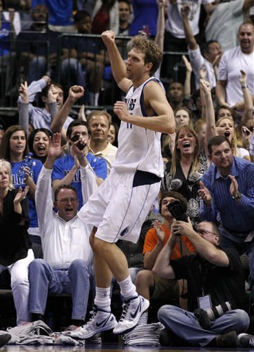 Fans cheer as Dallas Mavericks' Dirk Nowitzki, of Germany, celebrates a basket with a foul added on against the Houston Rockets late in the second half of an NBA basketball game on Wednesday, April 18, 2012, in Dallas. Nowitzki had a game-high 35 points in the 117-110 Mavericks win. (AP Photo/Tony Gutierrez)