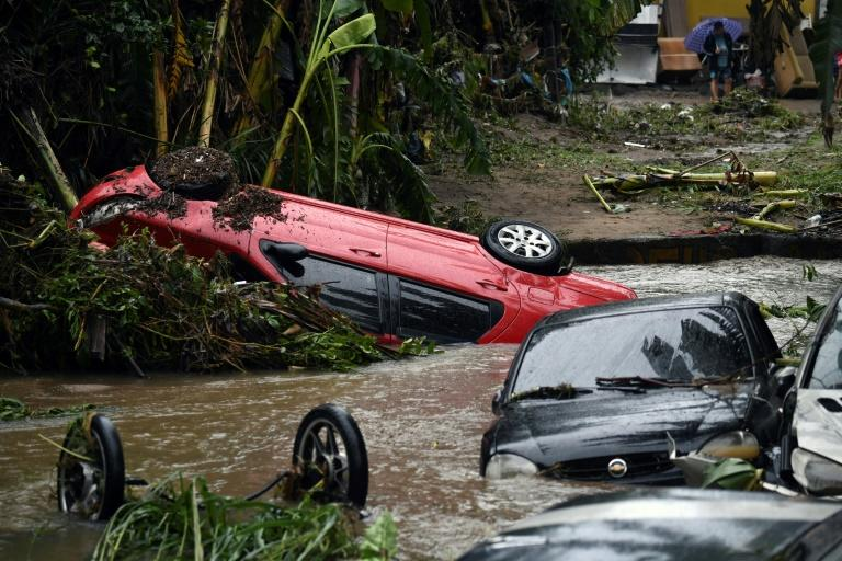 Heavy rain triggered flash floods that destroyed homes and swept away cars like these in Realengo, in the Rio de Janeiro suburbs (AFP Photo/MAURO PIMENTEL)