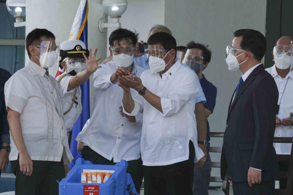 In this photo provided by the Presidential Communications Operations Office-Office of the Global Media Public Affairs, Philippine President Rodrigo Duterte, center, looks at a vial containing the Sinovac vaccine from China as it arrives at the Villamor Air Base in Manila, Philippines on Sunday Feb. 28, 2021. The Philippines is due to receive its first batch of COVID-19 vaccine Sunday, among the last in Southeast Asia to secure the critical doses despite having the second-highest number of coronavirus infections and deaths in the hard-hit region. (PCOO-OGMPA via AP)