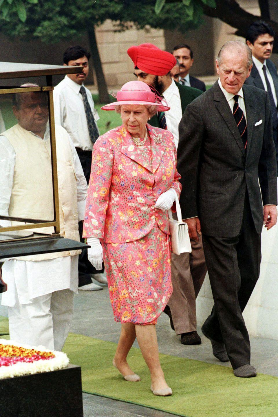 <p>The queen is dressed in a pink floral printed dress, matching blazer, and hat. Both she and Prince Philip removed their shoes, but kept on their socks, for a visit to the site of Gandhi's cremation in New Delhi, India. Walking barefoot on the grounds shows respect to the deceased. </p>