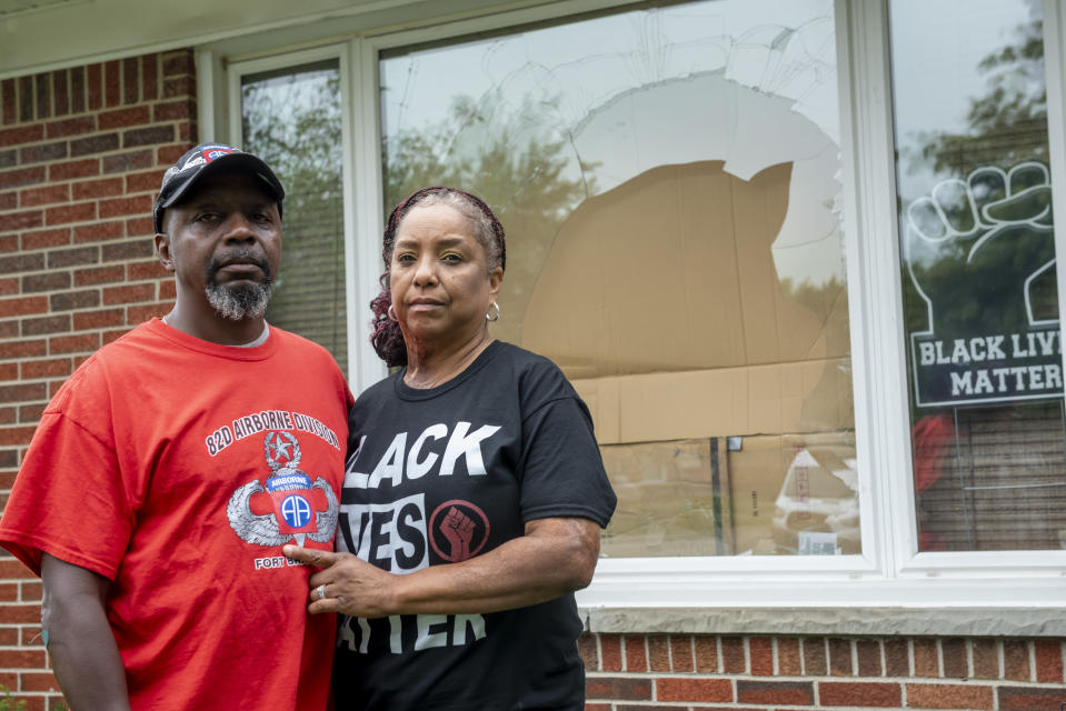 FILE - Eddie Hall Jr. and his wife Candace stand in front of the broken front window of their Warren, Mich., home, on Thursday, Sept. 10, 2020. Some experts say political and social unrest as well as the coronavirus pandemic has taken a disproportionate physical and financial tolls on Black people, resulting in increased anxiety levels among African Americans. (David Guralnick/Detroit News via AP, File)