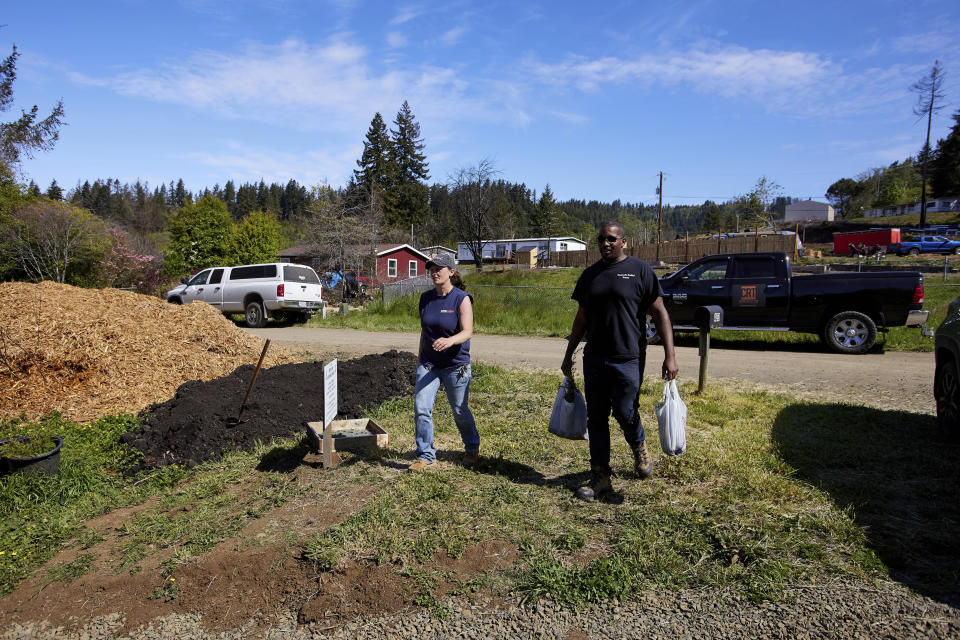 Melynda Small, left, and Marc Brooks, founder of Cascade Relief Team, walk to the Landscaping With Love greenhouse in Otis, Ore., on Thursday, May. 13, 2020. The greenhouse provides landscaping materials free to residents, helping the small town on the Oregon coast recover from the devastating fire that destroyed 293 homes. (AP Photo/Craig Mitchelldyer)