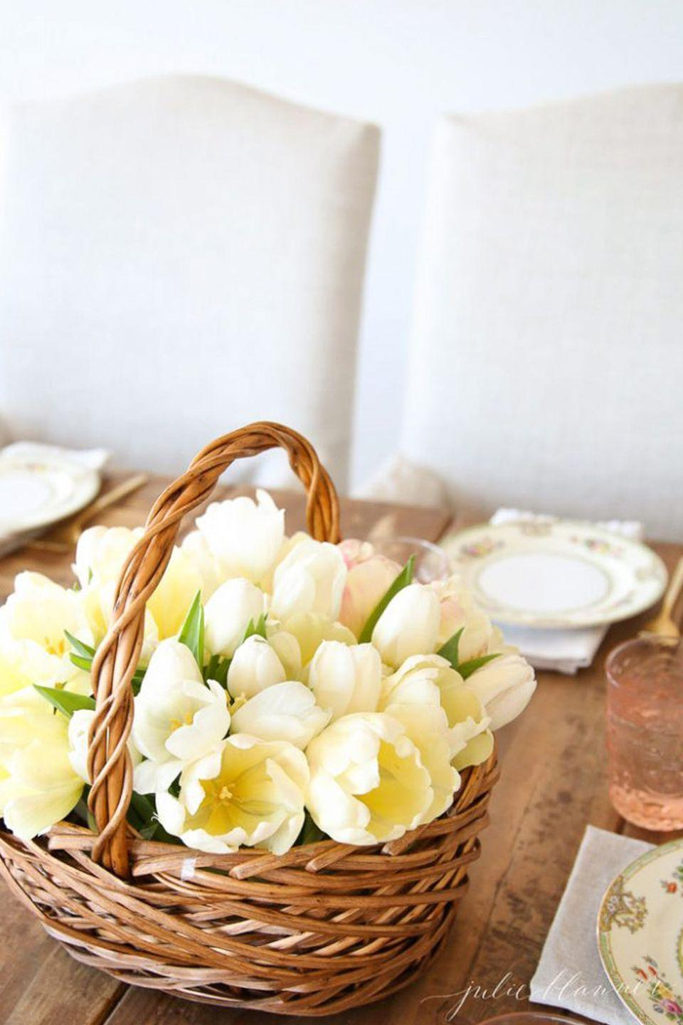 """<p>You can't go wrong with a white and cream bouquet of flowers, especially when they're nestled into a rustic, woven basket. </p><p><em><a href=""""https://julieblanner.com/basket-of-tulips-spring-centerpiece/"""" rel=""""nofollow noopener"""" target=""""_blank"""" data-ylk=""""slk:Get the tutorial at Julie Blanner »"""" class=""""link rapid-noclick-resp"""">Get the tutorial at Julie Blanner »</a></em></p><p><strong><em>Pottery Barn Artisan Vase, $79</em></strong> <a class=""""link rapid-noclick-resp"""" href=""""https://go.redirectingat.com?id=74968X1596630&url=https%3A%2F%2Fwww.potterybarn.com%2Fproducts%2Fartisan-ceramic-vase%2F&sref=https%3A%2F%2Fwww.housebeautiful.com%2Fentertaining%2Fflower-arrangements%2Fg19409803%2Feaster-flower-arrangements%2F"""" rel=""""nofollow noopener"""" target=""""_blank"""" data-ylk=""""slk:BUY NOW"""">BUY NOW</a></p>"""