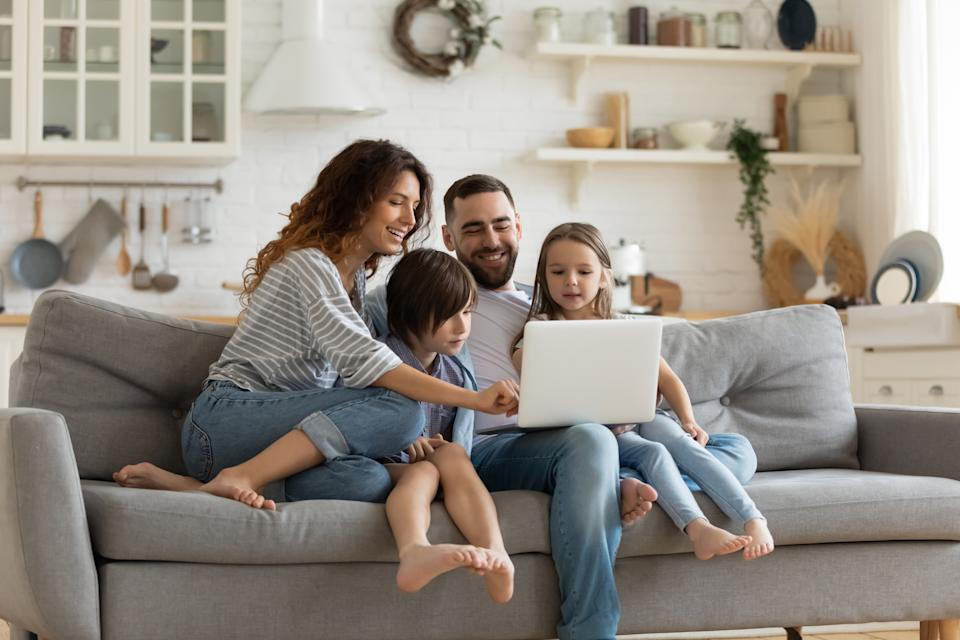 Happy young family with little kids sit on sofa in kitchen have fun using modern laptop together, smiling parents rest on couch enjoy weekend with small children laugh watch video on computer at home