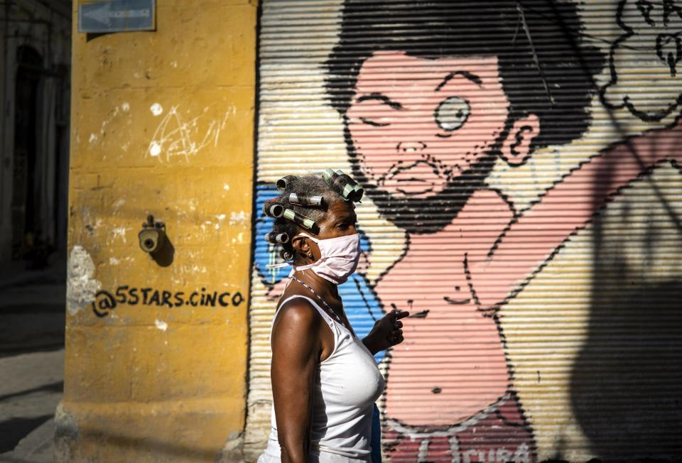 A woman wearing a mask as a precaution against the spread of the new coronavirus walks down the street in Havana, Cuba, Tuesday, March 31, 2020. Cuban authorities are requiring the use of masks for anyone outside their homes. (AP Photo/Ramon Espinosa)