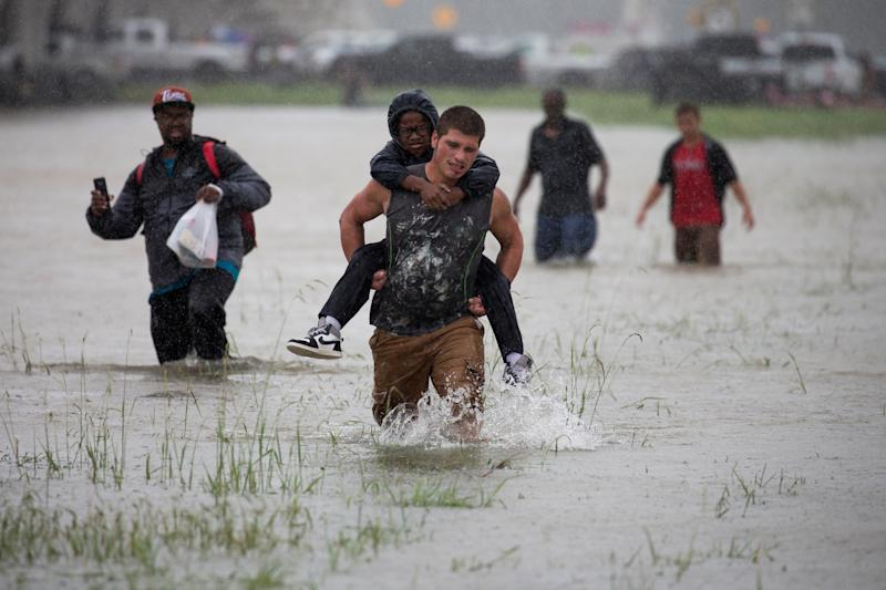 A man wades through flood waters from Tropical Storm Harvey while helping evacuate a boy in east Houston on Monday. (Adrees Latif / Reuters)