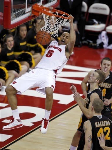 Wisconsin's Ryan Evans dunks in front of Milwaukee's James Haarsma (42), Kyle Kelm and Austin Arians, top, during the first half of an NCAA college basketball game Saturday, Dec. 22, 2012, in Madison, Wis. (AP Photo/Andy Manis)