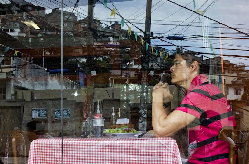 In this May 22, 2013 photo, a customer eats lunch at Bar Lacubaco in the Vidigal slum, reflected in the window in Rio de Janeiro, Brazil. With its view of the Atlantic's azure waters and its low prices, the Bar Lacubaco could give many conventional Rio restaurants a run for their money. In the land of the $35 martini, where a dinner for two routinely adds up to more than $200, Lacubaco's main courses are just $5-$7 apiece. (AP Photo/Victor R. Caivano)