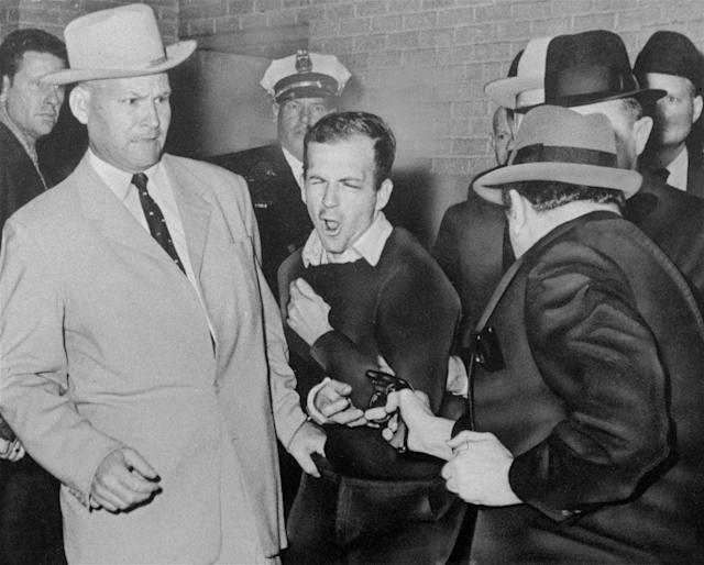 <p>Lee Harvey Oswald, assassin of President John F. Kennedy, reacts as Dallas night club owner Jack Ruby, foreground, shoots at him from point blank range in a corridor of Dallas police headquarters, Nov. 24, 1963. At left is Detective Jim Leavelle. Leavelle wanted to secretly take Oswald out the side door of Dallas police headquarters. His boss wanted to keep a promise to reporters. So Leavelle handcuffed himself to President Kennedy's assasin, stepped into a crowded basement and became an accidental part of history. (Photo: Dallas Times-Herald, Bob Jackson/AP) </p>