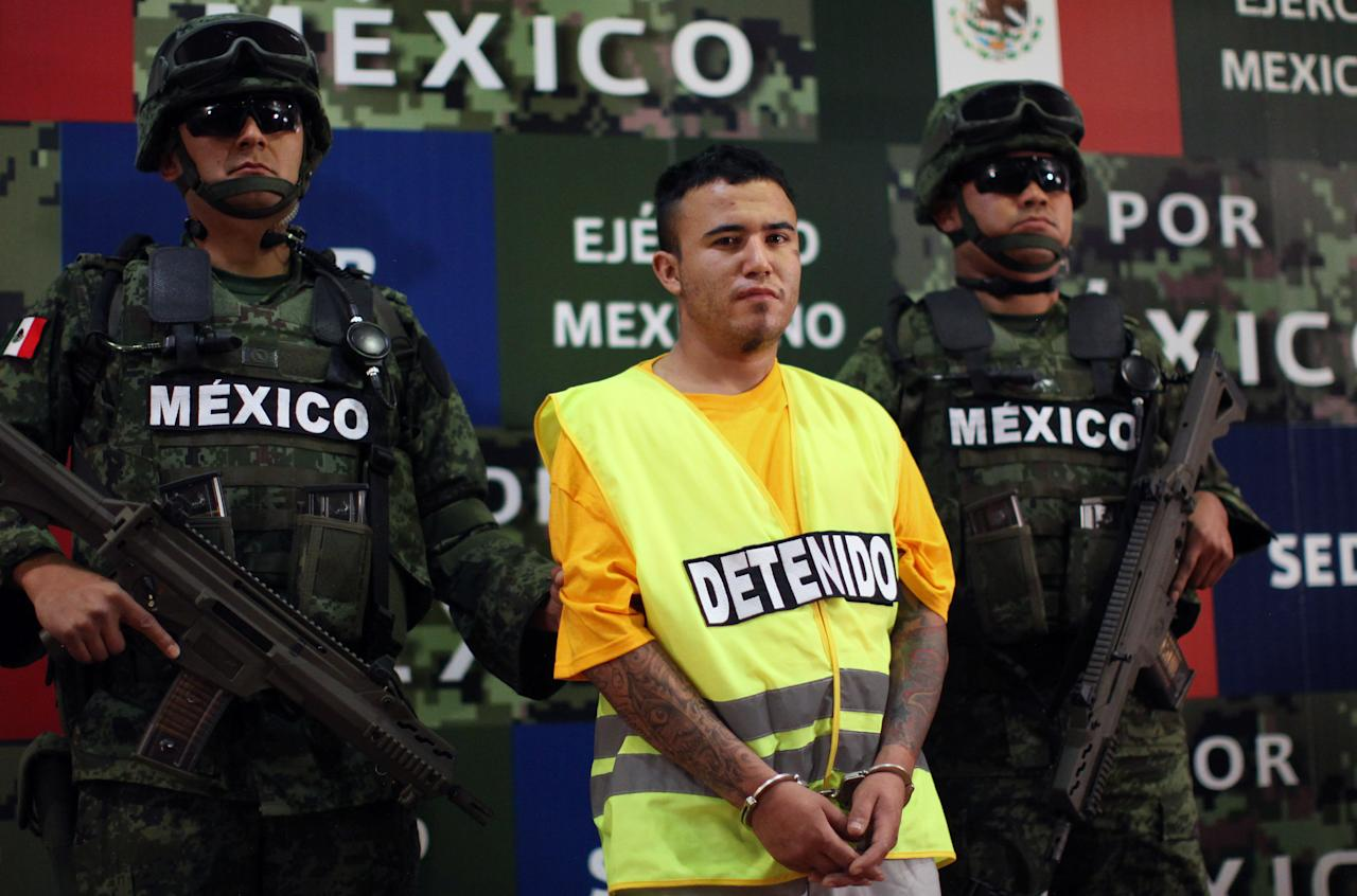 "Army soldiers flank Daniel Ramirez, alias ""El Loco,"" during his presentation to the media in Mexico City, Monday, May 21, 2012. Ramirez is believed to be a member of the Zetas drug cartel allegedly involved in the dumping of more than 40 hacked-up bodies on a highway outside the city of Cadereyta near Monterrey. The bodies with their heads, hands and feet hacked off were found May 13. (AP Photo/Alexandre Meneghini)"