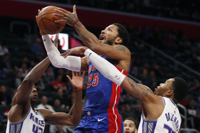 RETRANSMISSION TO CORRECT PLAYER AT RIGHT TO KENT BAZEMORE - Detroit Pistons guard Derrick Rose (25) attempts a layup as Sacramento Kings center Kent Bazemore, right, and forward Anthony Tolliver (43) defend during the first half of an NBA basketball game, Wednesday, Jan. 22, 2020, in Detroit. (AP Photo/Carlos Osorio)