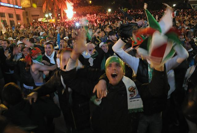 Algerian people celebrate their victory after the World Cup qualifying playoff second leg soccer match against Burkina Faso, in Algiers, Tuesday, Nov. 19, 2013. Algeria won 1-0 to qualify for the 2014 World Cup in Brazil. (AP Photo/Sidali Djarboub)