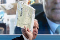 President Joe Biden holds up a map of wildfires in Washington state as he speaks with governors about ongoing efforts to strengthen wildfire prevention, preparedness and response efforts, and hear firsthand about the ongoing impacts of the 2021 wildfire season in the South Court Auditorium in the Eisenhower Executive Office Building on the White House Campus in Washington, Friday, July 30, 2021. (AP Photo/Andrew Harnik)