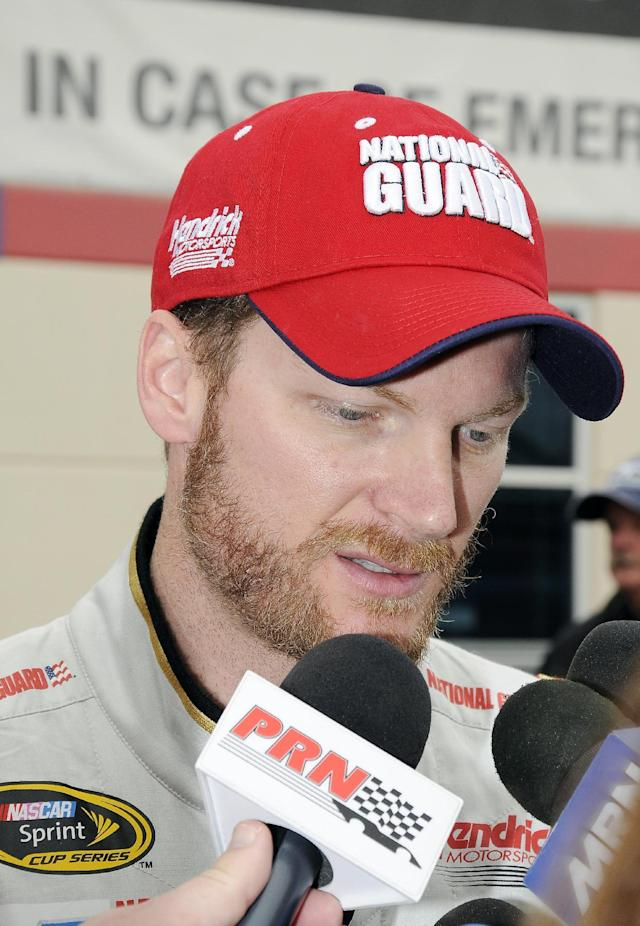 Dale Earnhardt Jr. is interviewed after his wreck during the NASCAR Sprint Cup series auto race at Texas Motor Speedway, Monday, April 7, 2014, in Fort Worth, Texas. (AP Photo/Larry Papke)