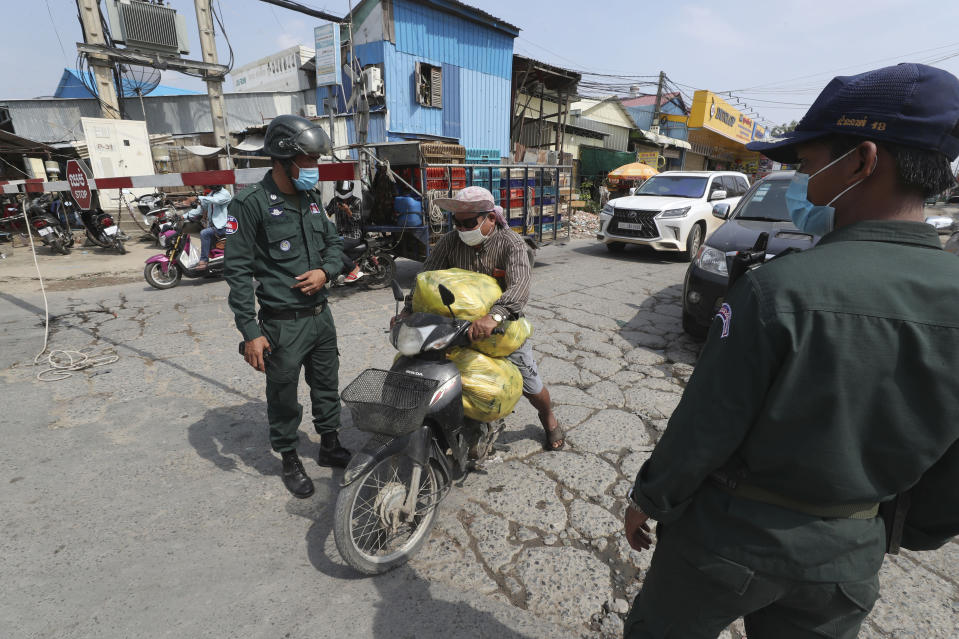A vendor, center, carries dead chickens for a nearby market as local police officers stand guard at a blocked street near Phnom Penh International airport in Phnom Penh, Cambodia, Thursday, April 15, 2021. Cambodia's leader said that the country's capital Phnom Penh will be locked down for two weeks from Thursday following a sharp rise in COVID-19 cases. (AP Photo/Heng Sinith)