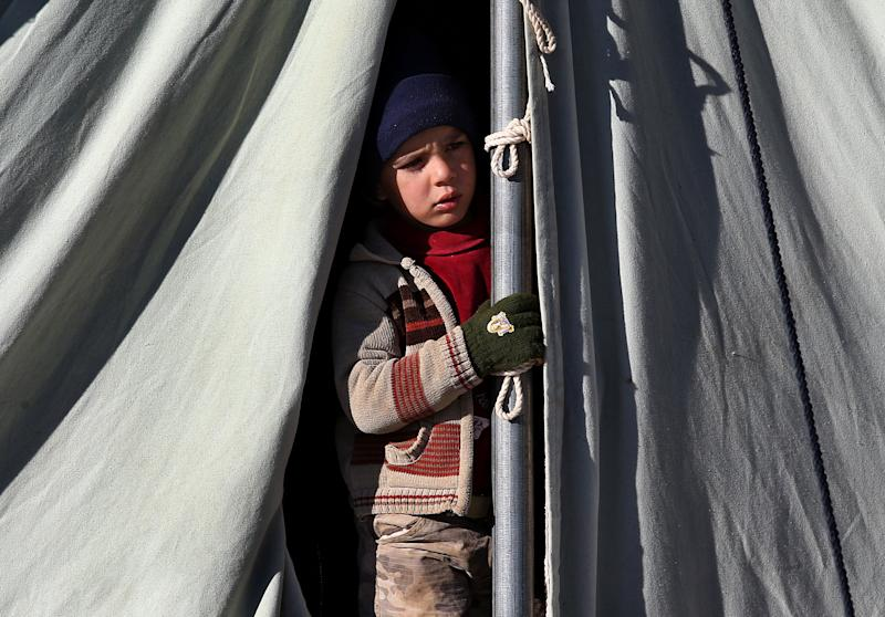A Syrian child looks out through his tent at a refugee camp in the eastern Lebanese border town of Arsal, Lebanon, Friday, Nov. 29, 2013. Every morning in northeastern Lebanon, hundreds of Syrian children are picked up from dozens of informal refugee settlements, loaded onto trucks and taken to the fields where they work for six to eight hours, earning up to four dollars a day. The kids are among a growing number of Syrian refugee children in Lebanon and Jordan who are fast becoming primary providers for families who lack resources for basic survival, according to a newly released report by the U.N. refugee agency. (AP Photo/Hussein Malla)