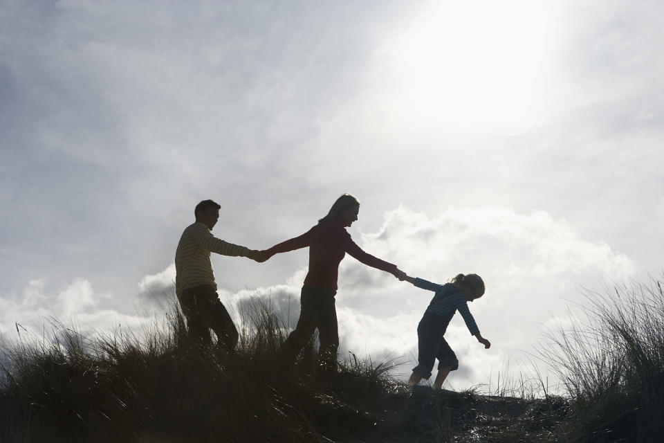Silhouette of parents and daughter (5-6) holding hands on sand dunes. Source: AAP