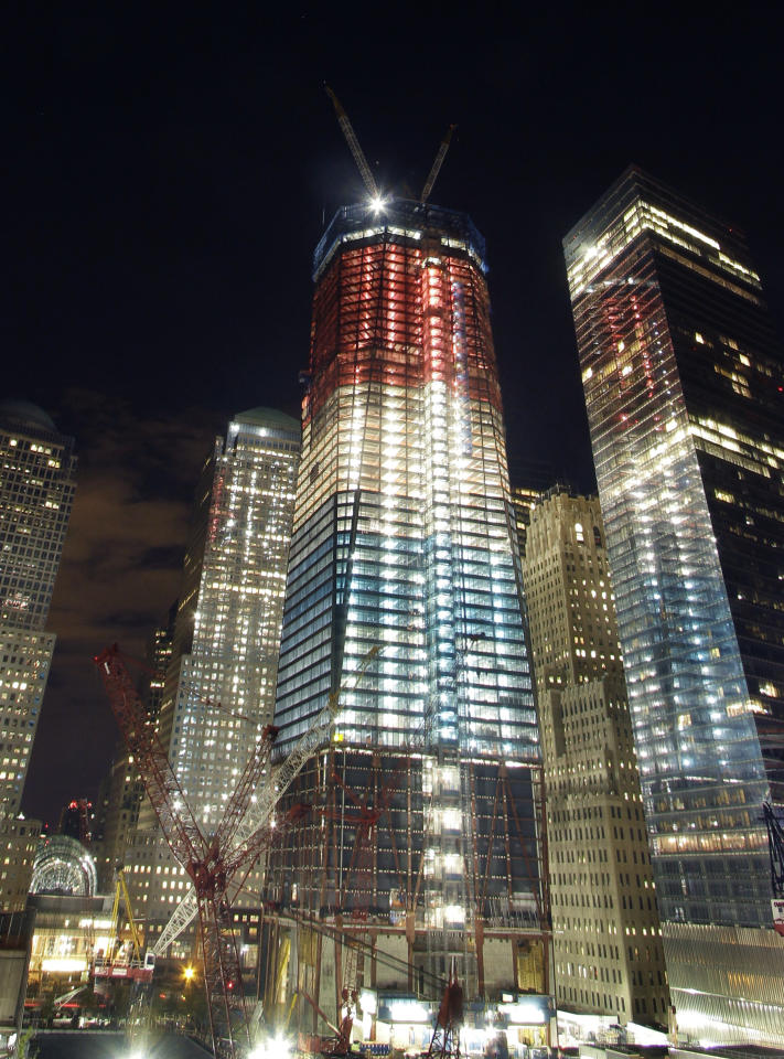 One World Trade Center, center, is illuminated in red, white, and blue prior to the visit of President Barack Obama to the September 11 Memorial, Thursday, May 5, 2011 in New York. Osama bin Laden, the mastermind of the September 11, 2001 attacks, was killed by U.S. forces in Pakistan, May 2, 2011. (AP Photo/Mark Lennihan)