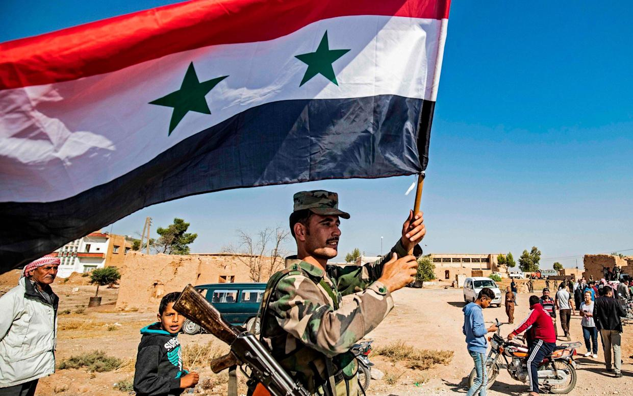 A Syrian regime soldier waves the national flag a street on the western entrance of the town of Tal Tamr in the countryside of Syria's northeastern Hasakeh province on October 14, 2019 - AFP