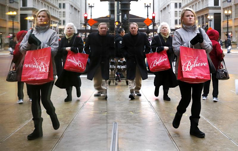 Last minute Christmas shoppers are reflected in a store's window as they walk through Chicago's Loop Wednesday, Dec. 24, 2014, in Chicago. (AP Photo/Charles Rex Arbogast)