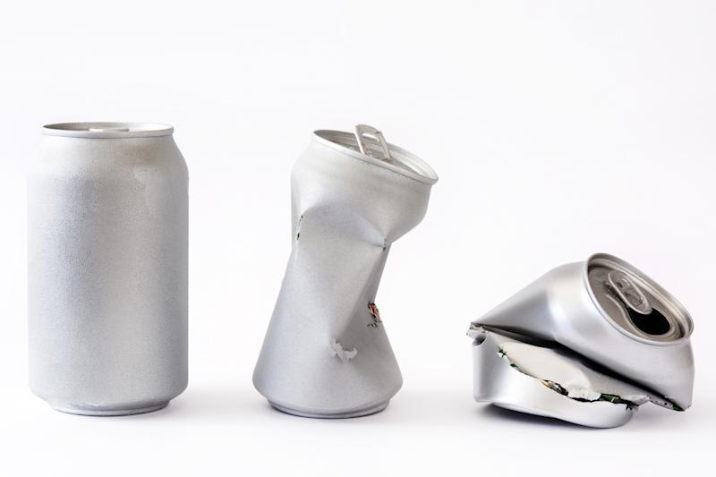 An intact beverage can, a partially crushed beverage can, and a fully crushed beverage can