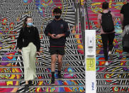 Spectators wearing masks walk past a hand sanitizer dispenser at court ahead of the first round matches at the Australian Open tennis championship in Melbourne, Australia, Monday, Feb. 8, 2021.(AP Photo/Hamish Blair)