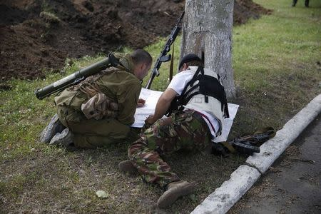 Pro-Russian separatists look at a map on their base in the east Ukrainian city of Donetsk May 30, 2014. REUTERS/Maxim Zmeyev