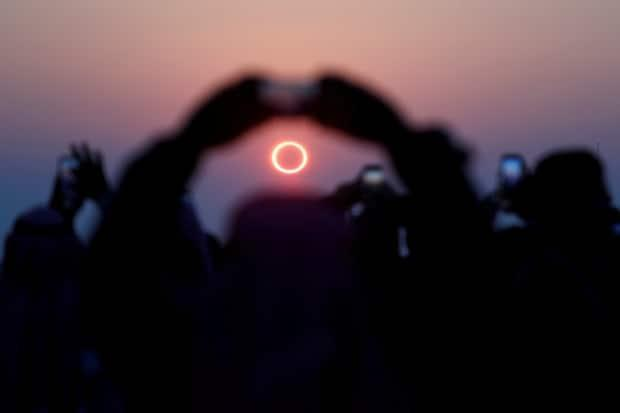 People take photos as they watch the annular solar eclipse on Jabal Arba (Four Mountains) in Hofuf, Saudi Arabia on Dec. 26, 2019. (Hamad I Mohammed/Reuters - image credit)