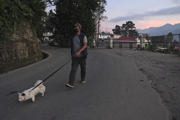 A Naga man wearing a face mask as a precautionary measure against the coronavirus walks his dog in Kohima, capital of the northeastern Indian state of Nagaland, Thursday, Oct. 29, 2020. India's confirmed coronavirus caseload surpassed 8 million on Thursday with daily infections dipping to the lowest level this week, as concerns grew over a major Hindu festival season and winter setting in. (AP Photo/Yirmiyan Arthur)