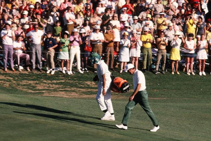 Masters Champion Charles Coody walks to the 18th green with his caddie, Walter Prichett, in the 1971 Masters Tournament