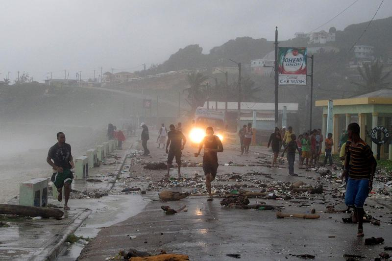 People run over a bridge covered by debris as waves hit the seawall, caused by Tropical Storm Isaac in Barahona, Dominican Republic, Friday, Aug. 24, 2012. Tropical Storm Isaac strengthened slightly as it spun toward the Dominican Republic and vulnerable Haiti on Friday, threatening to bring punishing rains but unlikely to gain enough steam to strike as a hurricane. (AP Photo/Ricardo Arduengo)