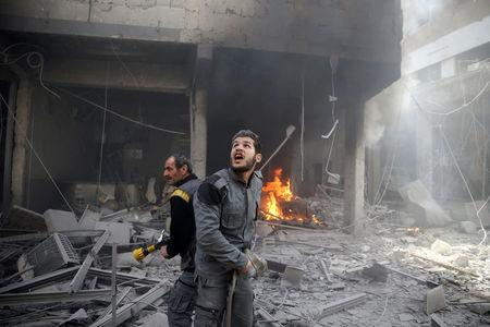 A Civil defence member reacts at a damaged site after an airstrike in the besieged town of Douma, Eastern Ghouta, Damascus, Syria February 9, 2018. REUTERS/Bassam Khabieh